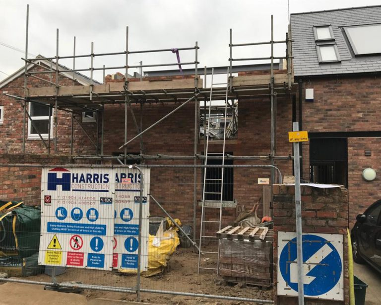 Outside view of a partially built town house by Harris Construction showing scaffolding and without the roof complete