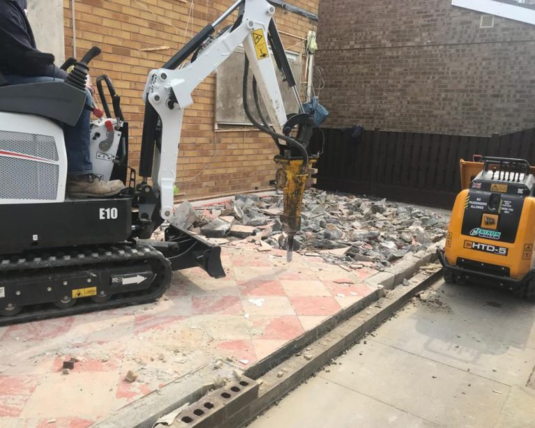 A digger digging the base during a house extension