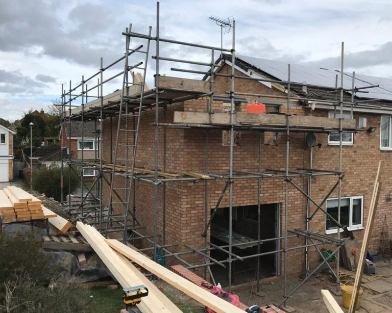 House extension in progress with scaffolding up and before the roof is complete