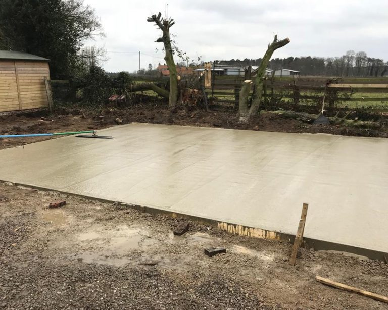 Ground work for a timber framed garage with a fresh concrete base