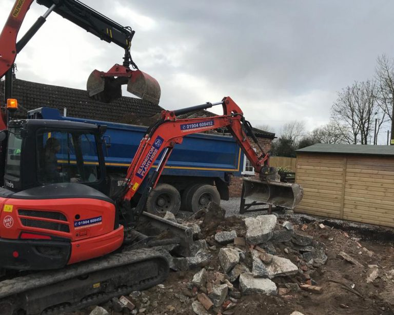 Ground work for a timber framed garage with a digger removing rubble